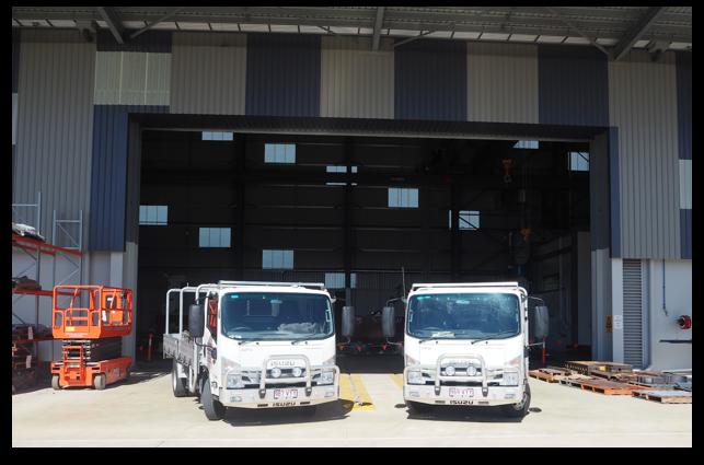 Two White Trucks In front of Roller Shutter Doors